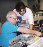 Instructor working with a student taking a computer apart